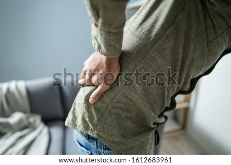 Man Having Backache While Sitting At Home