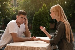 Man having boring date with talkative woman in outdoor cafe