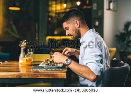 man having breakfast or dinner in cafe #1453086818