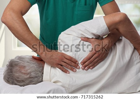 Man having chiropractic back adjustment. Osteopathy, Alternative medicine, pain relief concept. Physiotherapy, sport injury rehabilitation