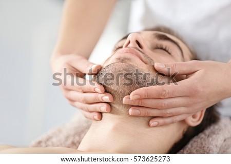 Man having face massage in spa salon