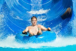 Man having fun, sliding at water park.