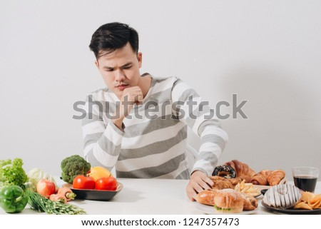 Man having hard choice between healthy and unhealthy food #1247357473