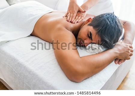 Man having massage in spa salon, closeup. Sports massage. Massage therapist massaging shoulders of a male athlete, working with Trapezius muscle. Young Man Enjoying Massage At Spa