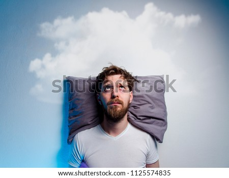 Man having problems/ insomnia, laying in bed on pillow, looking up to gray cloud over his head, copy space