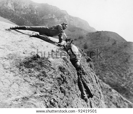 Man helping another man from falling down a cliff