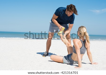 Man helping female runner in pain. Woman athlete having cramp during run. Sports woman with twisted sprained ankle, copys space.