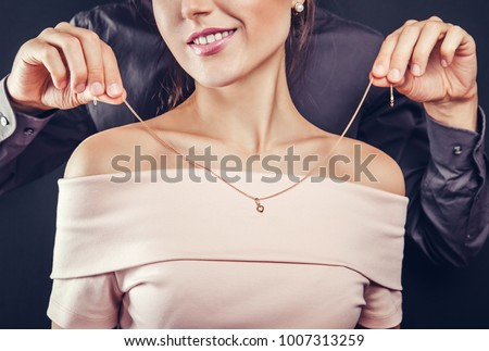 Man helping his girlfriend to try on a golden necklace on black background. Gift for Valentines day. Foto d'archivio ©