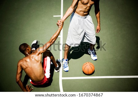 Man helping up player on outdoor basketball court