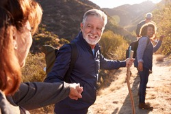Man Helping Woman On Trail As Group Of Senior Friends Go Hiking In Countryside Together