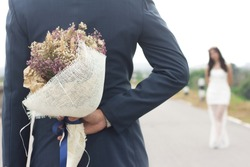 Man hiding behind a bouquet of flowers for marriage girlfriend request, will you marry me.