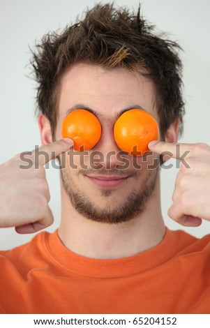Man hiding his eyes with mandarins