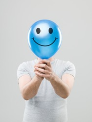 man hiding his face behing blue balloon with smiley face drawn on it, on grey background