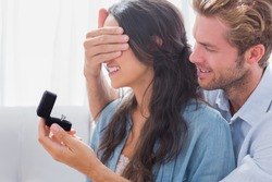 Man hiding his wifes eyes to offer her an engagement ring for a marriage proposal