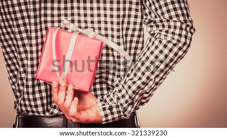 Man hiding pink gift box with white ribbon behind back. Closeup of male hand holding christmas present. Guy wearing flannel shirt. Birthday, holiday surprise. Instagram filtered.