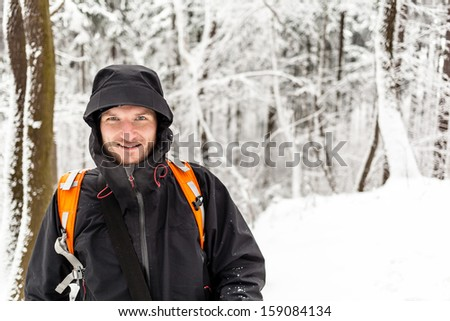 Man hiker hiking in white winter forest with backpack. Recreation and healthy lifestyle outdoors in snowy nature. Young male looking at camera and smiling.