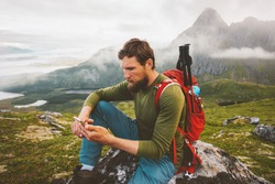 Man hiker using smartphone application navigation in mountains travel blogger influencer lifestyle hiking adventure summer trip outdoor backpacking in Norway