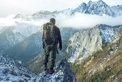 Man hiker with a backpack on top of the mountain back, looking at the snow slope. The concept of active relaxation, motivation and goal achievement