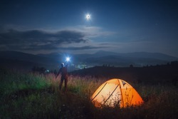 Man hiker with flashlight standing in a high grass on a hill near the camping tent. The moon eclipse in a night sky. Travel concept.
