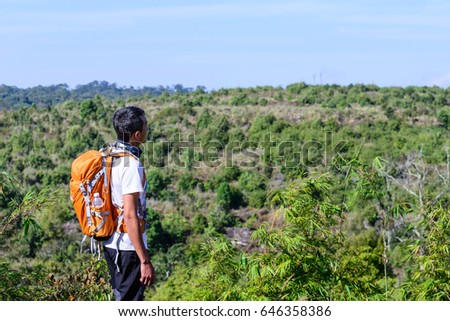 Man hiker with orange backpack looking view of mountain. #646358386