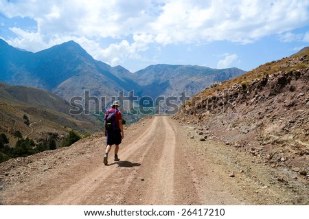 man hiking along track in atlas mountains, morocco