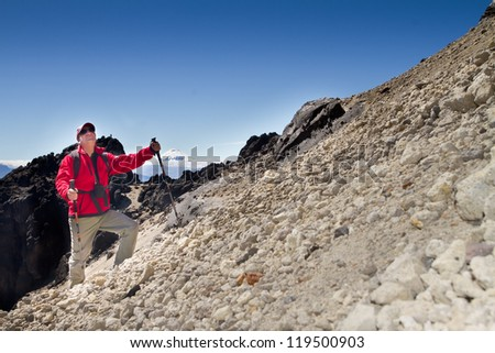 man hiking in a mountain, Cotopaxi volcano view with blue skyes