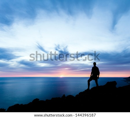 Man hiking silhouette in mountains sunset and ocean Male hiker with backpack on top of mountain looking at beautiful night landscape