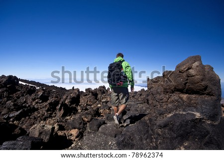 Man hiking. Young  guy hiking / backpacking in the rough  volcanic landscape on the volcano, Teide, highest peak of Spain.