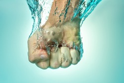Man hit the water from above. The concept of strength and self-confidence. Blue background.