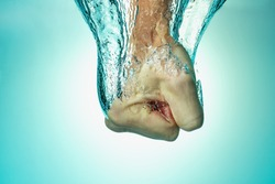 Man hit the water, the concept of strength and self-confidence, assertiveness and success. Close up on a blue background. from above.