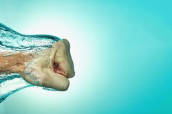 Man hit the water, the concept of strength and self-confidence, assertiveness and success. Close up on a blue background.