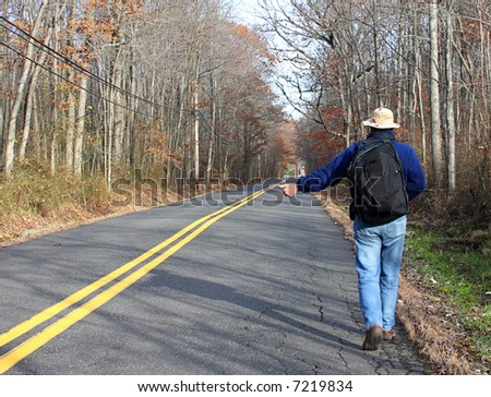 Man hitchhiking along a country road in fall carrying a backpack