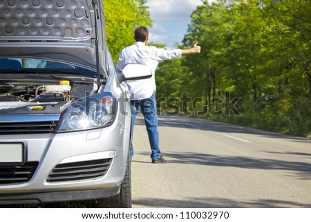 Man hitchhiking by a broken car