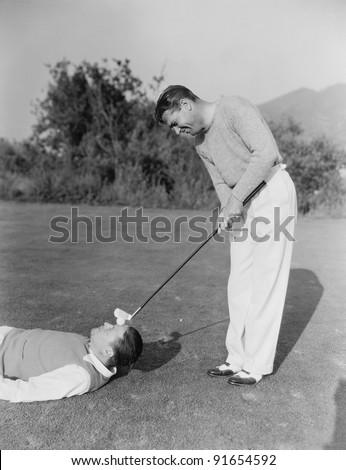 Man hitting golf ball on mans forehead
