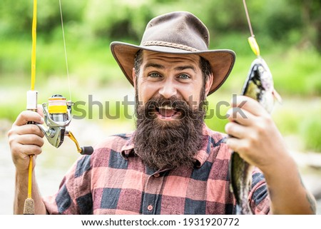 Man hold big fish trout in his hands. Fisherman and trophy trout. Man holding a trout fish. Fishing. Angler with fishing trophy. Fisherman and trout. Fishing backgrounds.