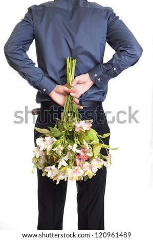 Man hold bouquet of flowers behind his back.  isolated on white background