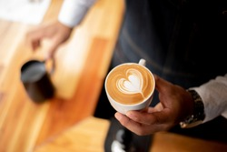 man hold coffee cup with heart on there