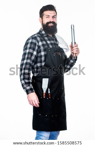 Man hold cooking utensils barbecue. Tools for roasting meat outdoors. Picnic and barbecue. Cooking meat in park. Barbecue master. Bearded hipster wear apron for barbecue. Roasting and grilling food.