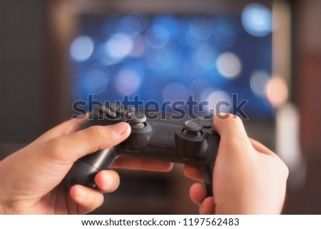 Man hold game pad in front of tv screen #1197562483