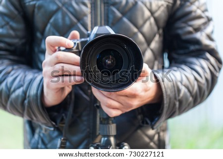 Man hold photo camera. Outdoor.