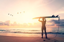 Man hold surfboard standing with birds flying at tropical sunset beach background. Summer vacation and sport adventure concept. Vintage tone filter effect color style.