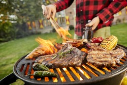 Man holding a beer grilling meat on a BBQ outdoors in his garden turning the sausages with tongs in a close up view on the beef steaks, corncob, chili peppers and chicken breast