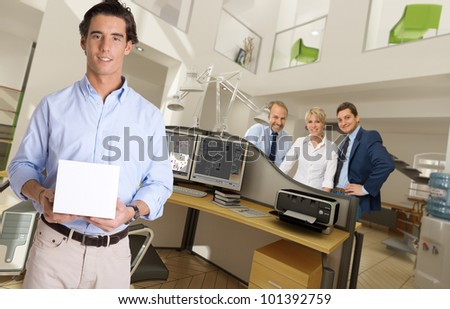 Man holding a blank box in a modern office