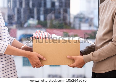 Man holding a book and clothes donate box. Donation concept.