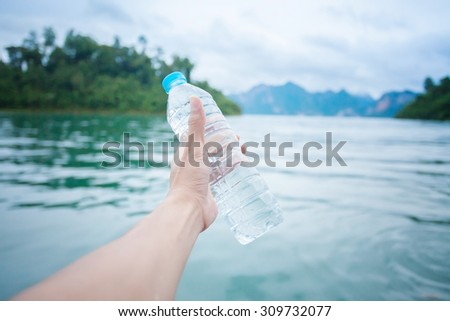 Man holding a bottle of water at lake, health care, healthy