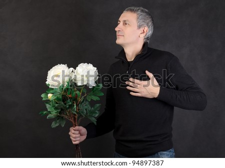 Man holding a bouquet of flowers on gray background - stock photo