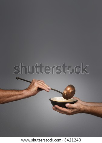 man holding a bowl in both hands, receiving a serving of soup from another man holding a soup ladle