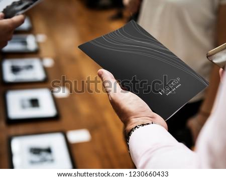 Man holding a brochure mockup in an art gallery #1230660433
