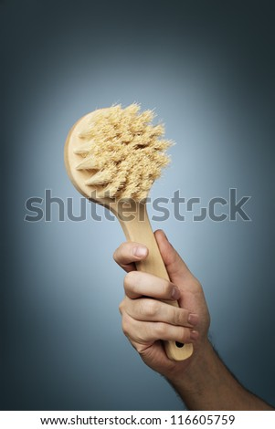 Man holding a brush made of wood and natural fibers in his hand.