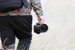 Man holding a camera walking outdoors. Caucasian wildlife photographer with bagpack and a telephoto lens trekking on a yellow grass field. Concept of widlife photography and nature activities.